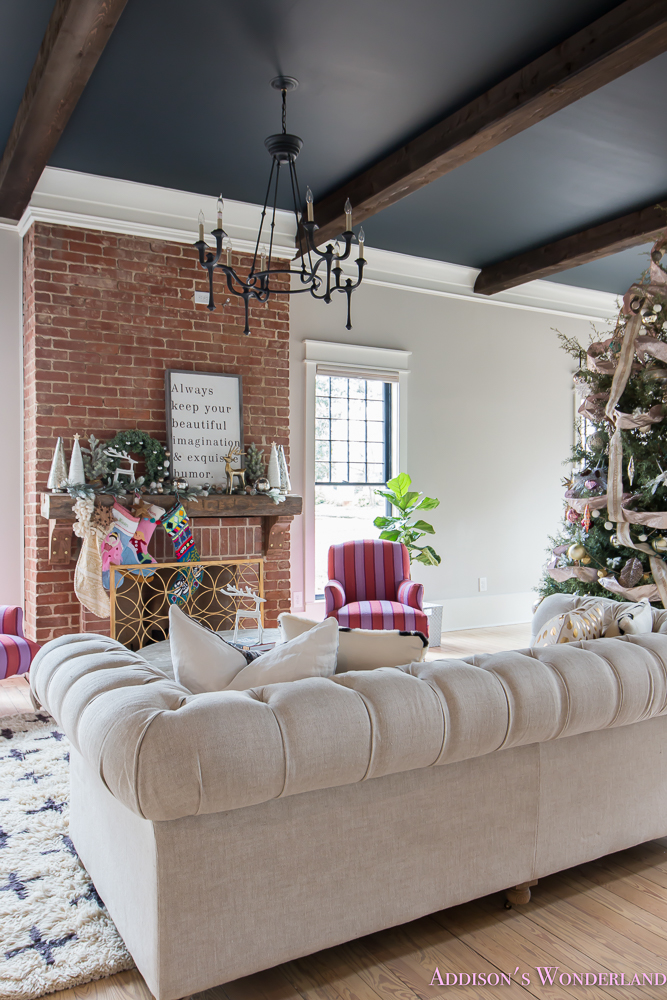 vintage-living-room-black-ceiling-brick-fireplace-dark-wood-beams-anthropologie-home-tufted-sofa-christmas-2-of-23