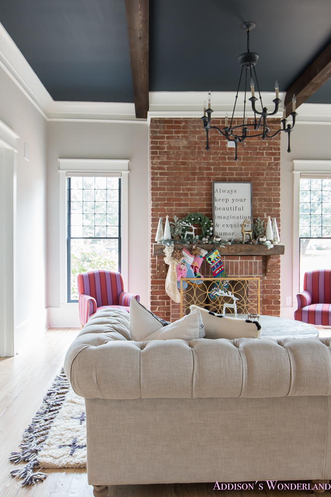 vintage-living-room-black-ceiling-brick-fireplace-dark-wood-beams-anthropologie-home-tufted-sofa-christmas-3-of-23