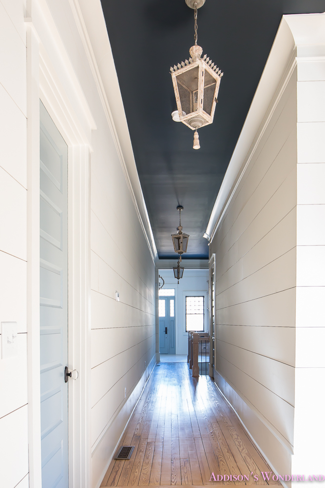 hallway-white-walls-shiplap-black-ceiling-alabaster-inkwell-lantern-chateau-blue-door-stardew-uncertain-grey-whitewashed-hardwood-flooring-1-of-15
