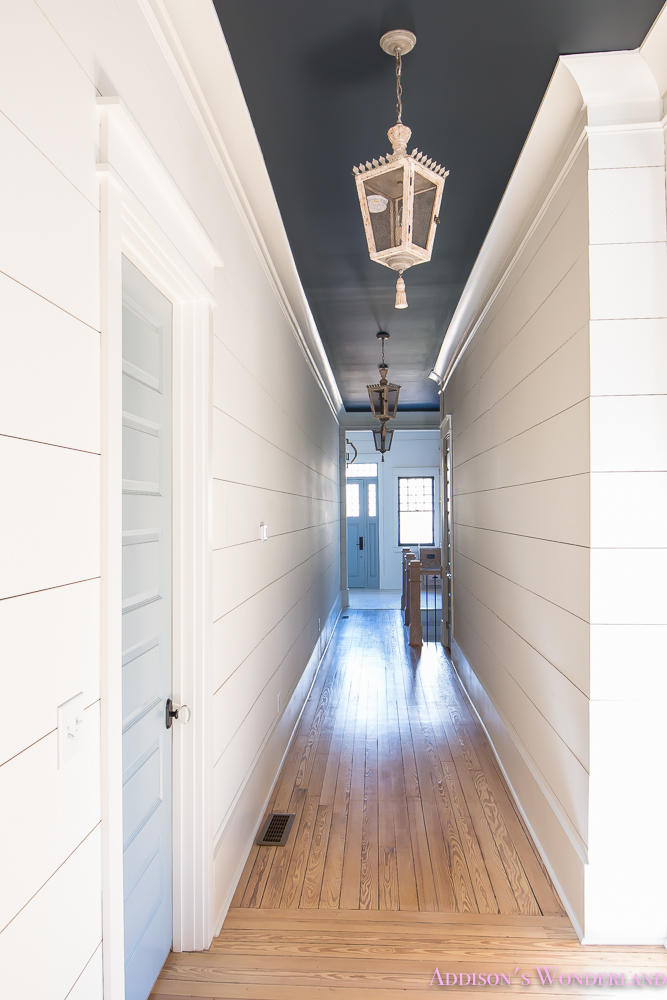 hallway-white-walls-shiplap-black-ceiling-alabaster-inkwell-lantern-chateau-blue-door-stardew-uncertain-grey-whitewashed-hardwood-flooring-2-of-15