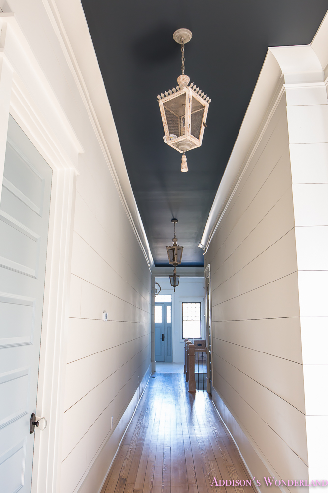 hallway-white-walls-shiplap-black-ceiling-alabaster-inkwell-lantern-chateau-blue-door-stardew-uncertain-grey-whitewashed-hardwood-flooring-3-of-15