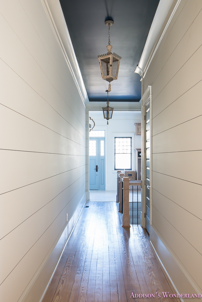 hallway-white-walls-shiplap-black-ceiling-alabaster-inkwell-lantern-chateau-blue-door-stardew-uncertain-grey-whitewashed-hardwood-flooring-4-of-15