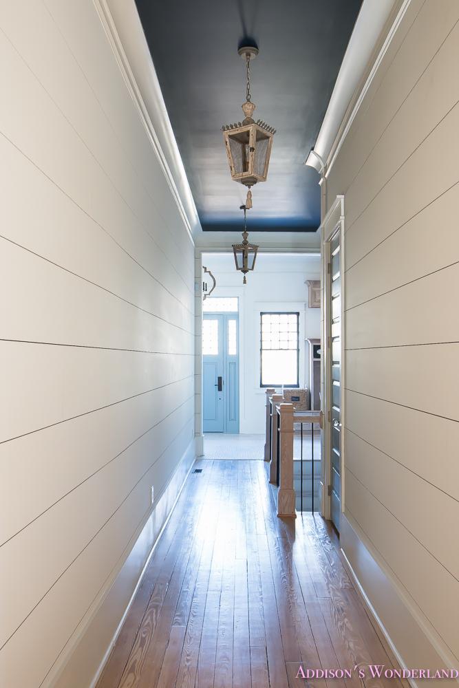 hallway-white-walls-shiplap-black-ceiling-alabaster-inkwell-lantern-chateau-blue-door-stardew-uncertain-grey-whitewashed-hardwood-flooring-4-of-15
