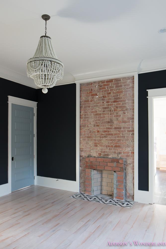 master-bedroom-black-walls-shaw-hardwood-whitewashed-wood-floors-brick-fireplace-white-beaded-chandelier-1-of-7
