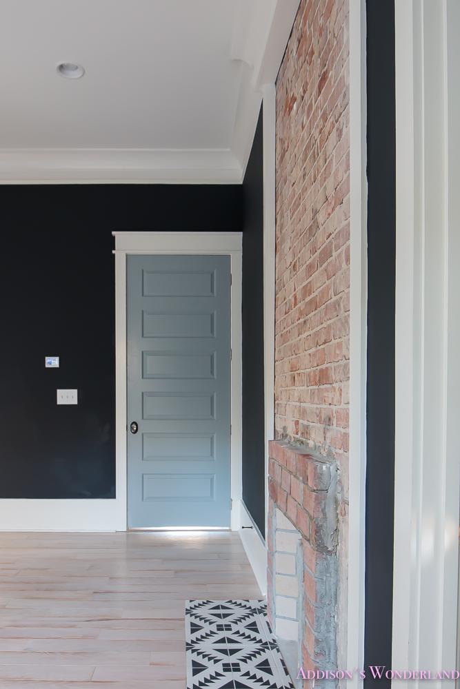 master-bedroom-black-walls-shaw-hardwood-whitewashed-wood-floors-brick-fireplace-white-beaded-chandelier-7-of-7