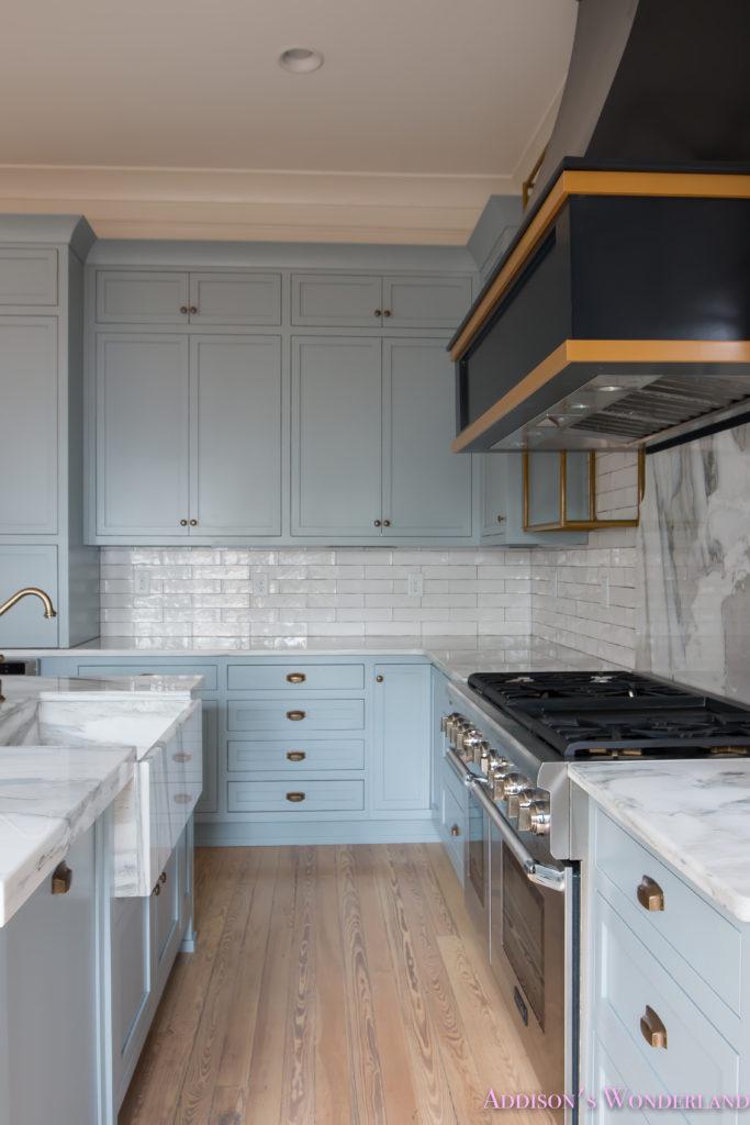 a-classic-vintage-modern-kitchen-blue-gray-cabinets-inset-shaker-black-gold-vent-hood-antique-brass-faucet-white-subway-backsplash-tile-gold-open-shelves-12-of-16