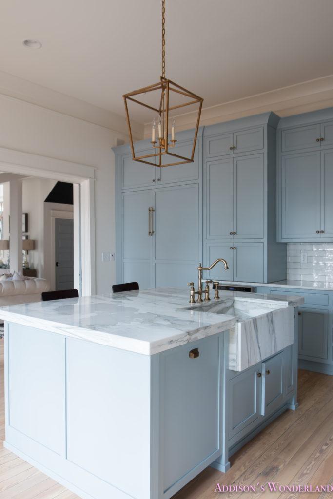 a-classic-vintage-modern-kitchen-blue-gray-cabinets-inset-shaker-black-gold-vent-hood-antique-brass-faucet-white-subway-backsplash-tile-gold-open-shelves-9-of-16