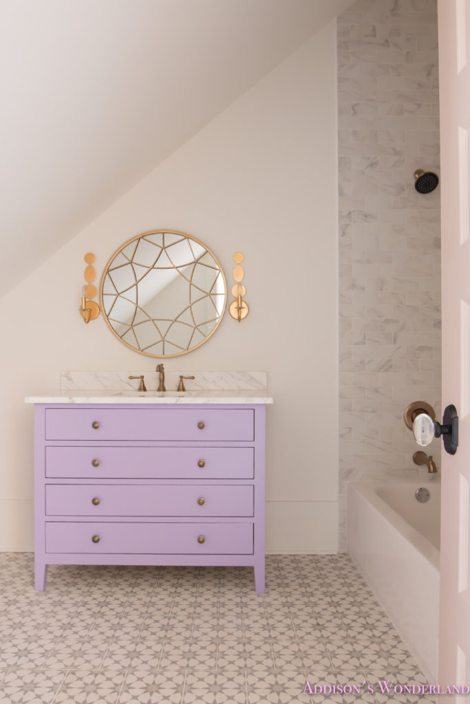 alabaster-walls-girls-bathroom-white-porcelain-marble-subway-tile-cement-tile-patterned-antique-brass-faucet-purple-vanity-cabinet-1-of-6