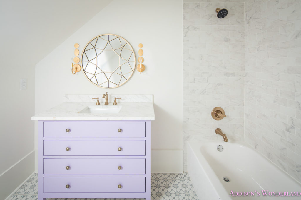 alabaster-walls-girls-bathroom-white-porcelain-marble-subway-tile-cement-tile-patterned-antique-brass-faucet-purple-vanity-cabinet-4-of-4