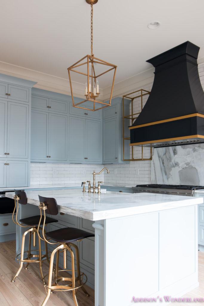 classic-vintage-modern-kitchen-blue-gray-cabinets-inset-shaker-black-gold-vent-hood-antique-brass-faucet-white-subway-backsplash-tile-gold-open-shelves-13-of-18