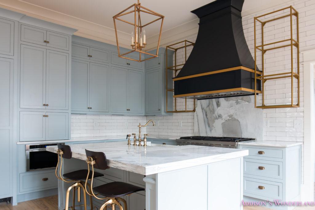 classic-vintage-modern-kitchen-blue-gray-cabinets-inset-shaker-black-gold-vent-hood-antique-brass-faucet-white-subway-backsplash-tile-gold-open-shelves-14-of-18