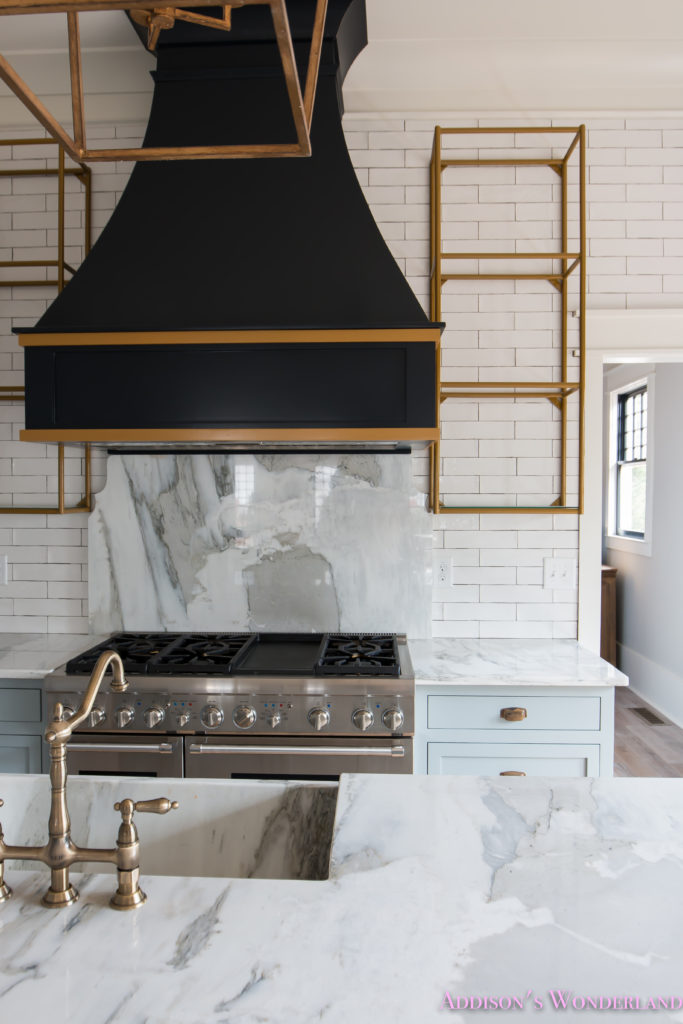 classic-vintage-modern-kitchen-blue-gray-cabinets-inset-shaker-black-gold-vent-hood-antique-brass-faucet-white-subway-backsplash-tile-gold-open-shelves-18-of-18