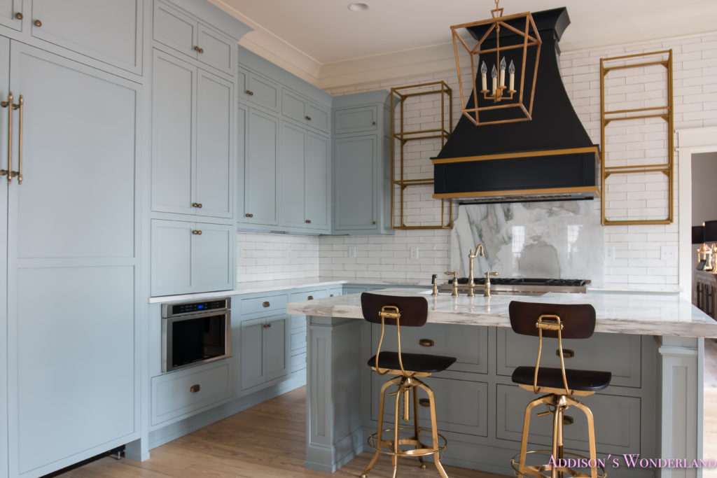classic-vintage-modern-kitchen-blue-gray-cabinets-inset-shaker-black-gold-vent-hood-antique-brass-faucet-white-subway-backsplash-tile-gold-open-shelves-7-of-18