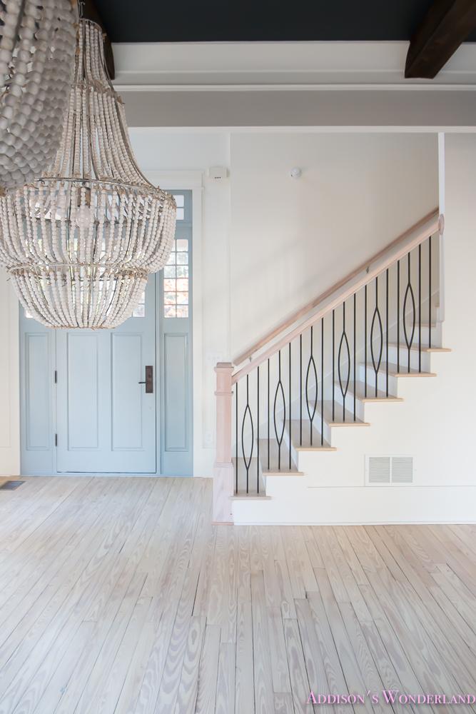 foyer-white-walls-blue-front-foor-uncertain-grey-stardew-alabaster-sherwin-williams-iron-baluster-staircase-whitewashed-hardwood-floors-1-of-5