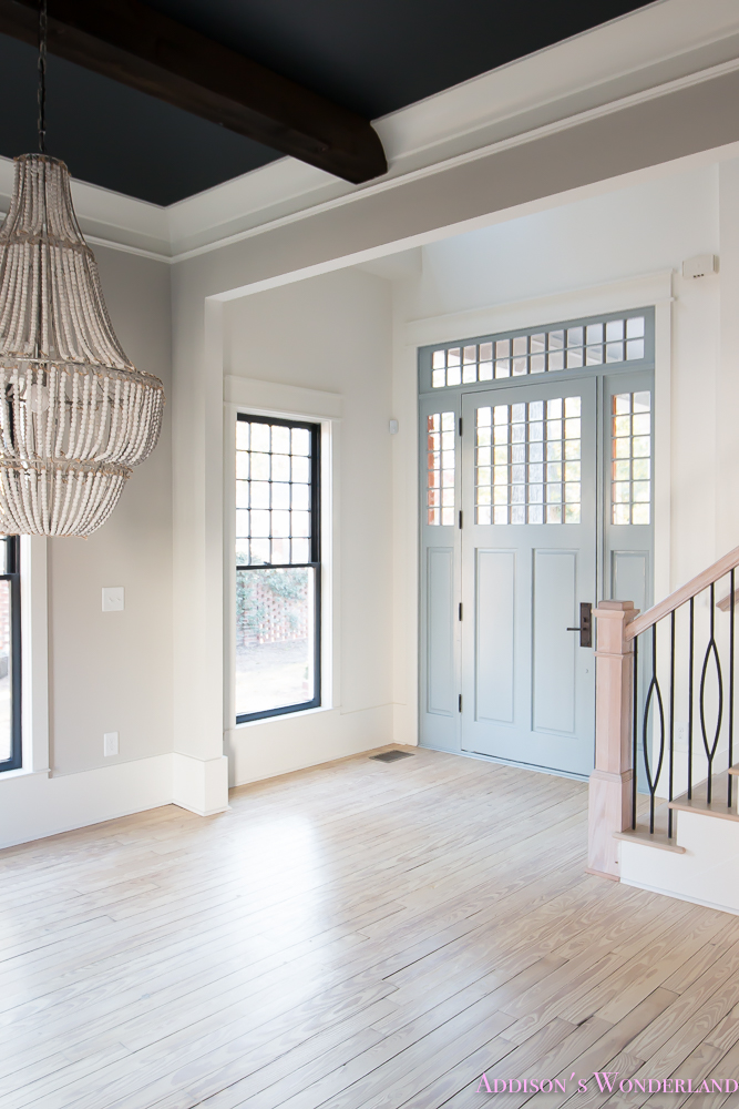 foyer-white-walls-blue-front-foor-uncertain-grey-stardew-alabaster-sherwin-williams-iron-baluster-staircase-whitewashed-hardwood-floors-2-of-5