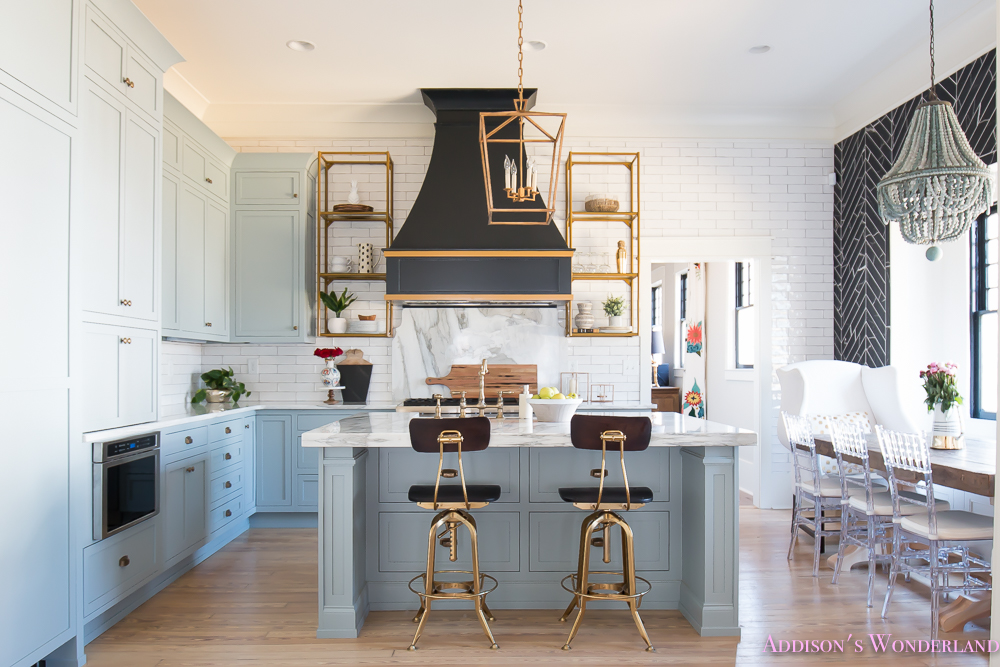 kitchen-white-marble-calcutta-gold-open-shelves-gold-black-vent-hood-blue-gray-cabinets-shaker-style-black-chevron-tile-subway-white-backsplash-decor-ideas-1-of-32