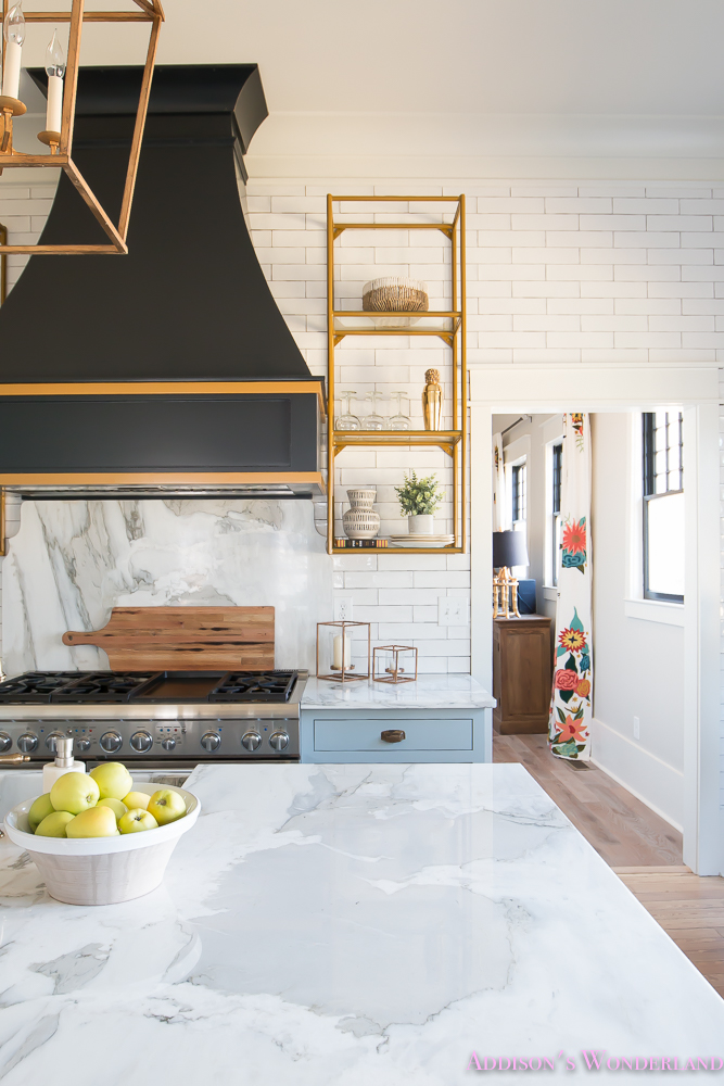 kitchen-white-marble-calcutta-gold-open-shelves-gold-black-vent-hood-blue-gray-cabinets-shaker-style-black-chevron-tile-subway-white-backsplash-decor-ideas-10-of-32