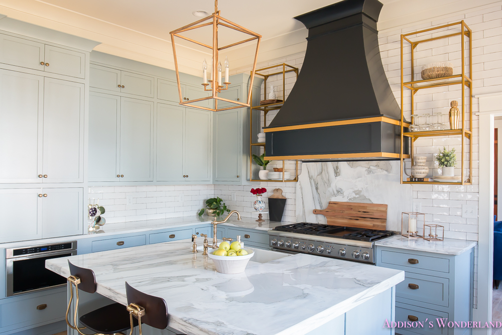kitchen-white-marble-calcutta-gold-open-shelves-gold-black-vent-hood-blue-gray-cabinets-shaker-style-black-chevron-tile-subway-white-backsplash-decor-ideas-12-of-32