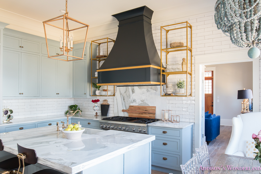 kitchen-white-marble-calcutta-gold-open-shelves-gold-black-vent-hood-blue-gray-cabinets-shaker-style-black-chevron-tile-subway-white-backsplash-decor-ideas-13-of-32