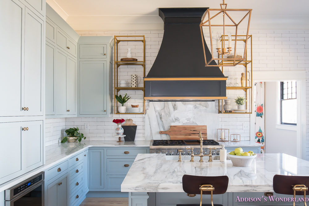 kitchen-white-marble-calcutta-gold-open-shelves-gold-black-vent-hood-blue-gray-cabinets-shaker-style-black-chevron-tile-subway-white-backsplash-decor-ideas-16-of-32