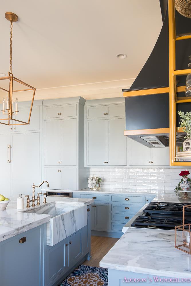 kitchen-white-marble-calcutta-gold-open-shelves-gold-black-vent-hood-blue-gray-cabinets-shaker-style-black-chevron-tile-subway-white-backsplash-decor-ideas-20-of-32
