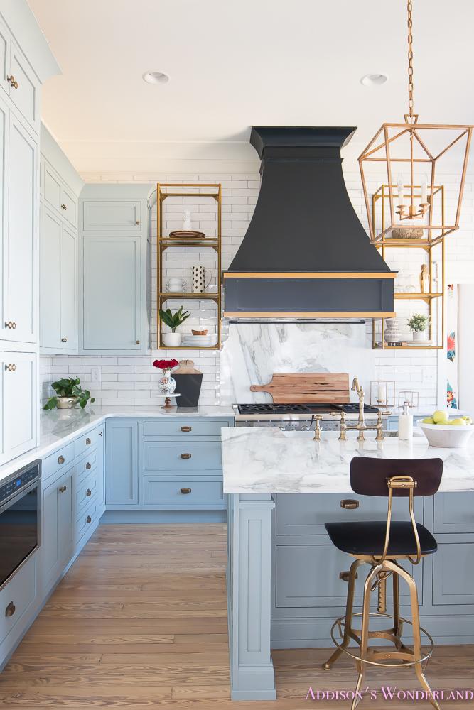 kitchen-white-marble-calcutta-gold-open-shelves-gold-black-vent-hood-blue-gray-cabinets-shaker-style-black-chevron-tile-subway-white-backsplash-decor-ideas-5-of-32